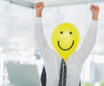 Yellow balloon with cheerful face replacing businessmans face