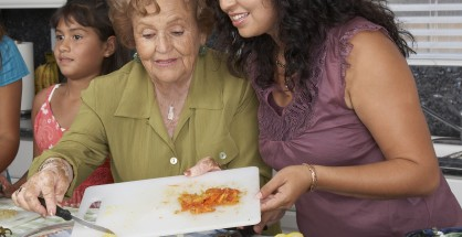 Multi-generational Hispanic female family members preparing food