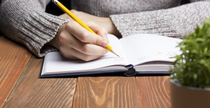 female hands with pencil writing on notebook.